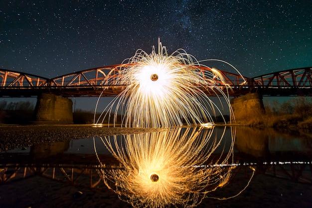 Licht schilderij kunst concept. spinnende staalwol in abstracte cirkel, vuurwerkdouches van felgele gloeiende schittert op lange brug weerspiegeld in rivierwater op blauwe nacht sterrenhemel