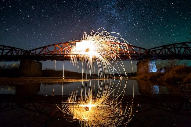 Licht schilderij kunst concept. spinnende staalwol in abstracte cirkel, vuurwerkdouches van heldergele gloeiende fonkelingen op lange brug weerspiegelden in rivierwater op de blauwe achtergrond van de nacht sterrige hemel.