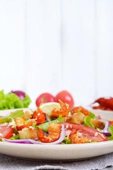 Licht smakelijke salade met garnalen, sla, knoflook en croutons