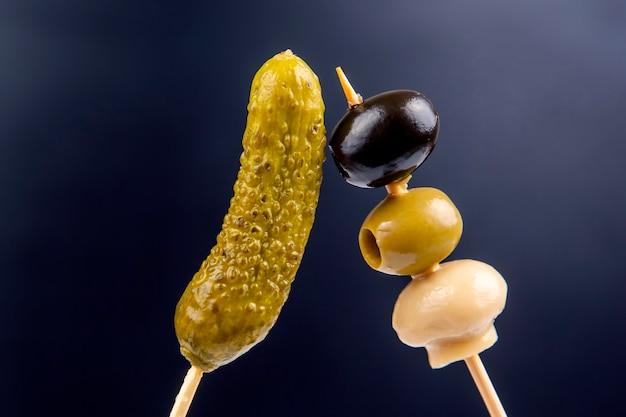 Licht sneeuwontbijt van ingeblikte en ingelegde komkommers, olijven en champignons op een donkerblauwe achtergrond. voedsel en groenten. dieet en gewichtsverlies