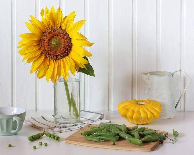 Licht stilleven met zonnebloem en groenten op tafel