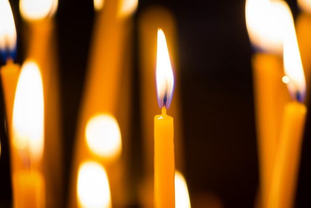 Licht van kaarsen in de kerk op zwart
