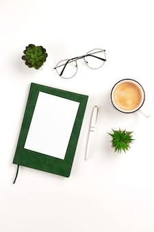 Licht verticaal ansichtkaartmodel voor ontwerppresentatie op een witte werkplek met koffienotitieboekjepen...