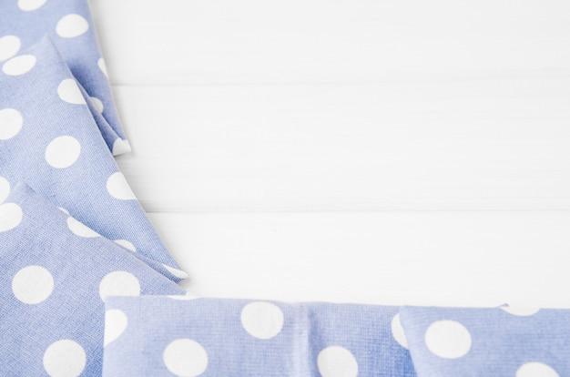 Licht violet blauw polka dots gevouwen tafelkleed over gebleekte houten tafel. bovenaanzicht afbeelding. copyspace voor uw tekst.