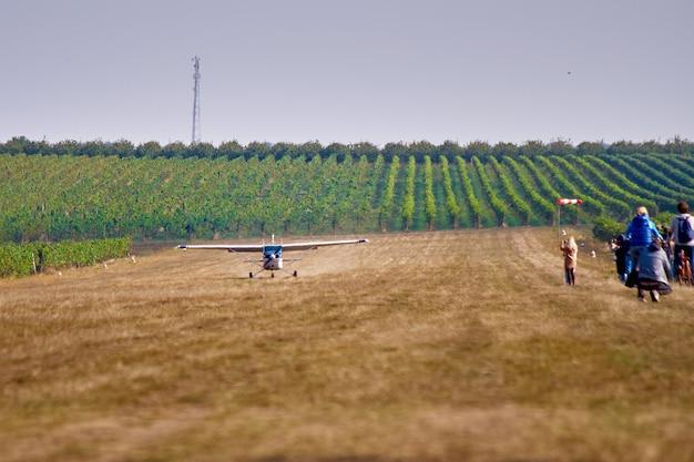 Licht vliegtuig. een licht vliegtuig landt in een veld bij een wijngaard