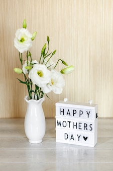 Lichtbak met belettering happy mother's day, witte bloemen eustoma of lisianthus in vaas op houten tafel.