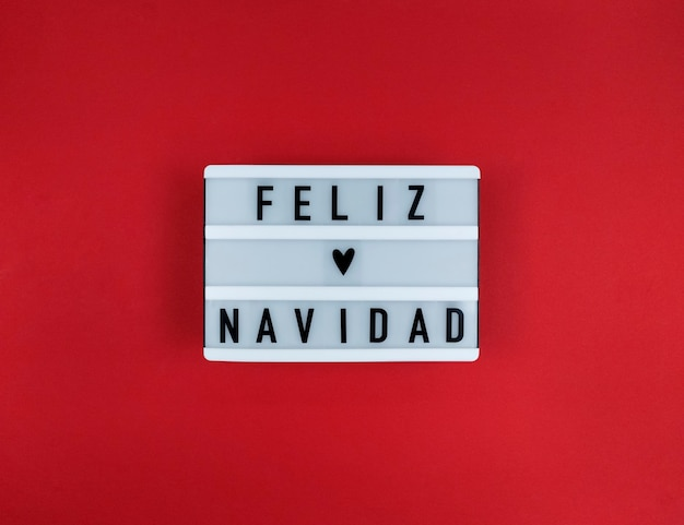 Lichtbak met feliz navidad zin, spaans merry christmas op een rode achtergrond.