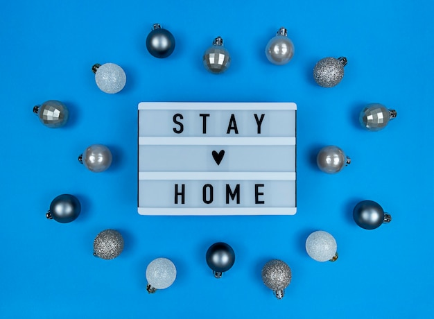Lichtbak met quote voor thuisblijvers met kerstballen.