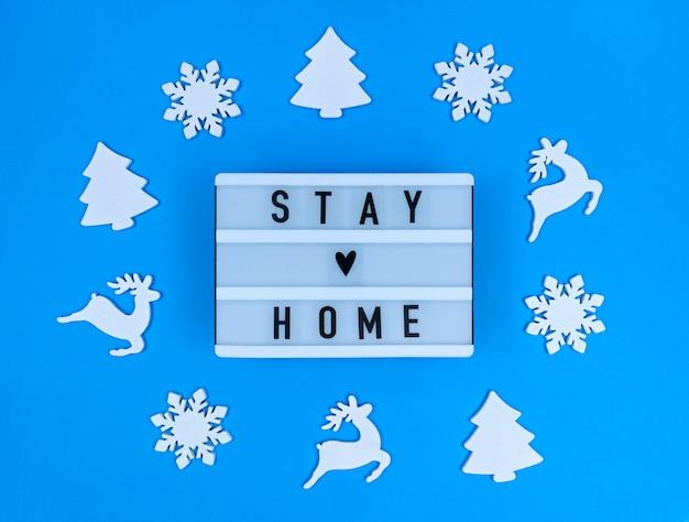 Lichtbak met stay home quote met kerstspeelgoed. Premium Foto