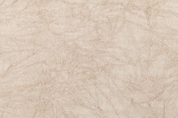 Lichtbeige golvende achtergrond van textiel. stof met natuurlijke textuur clousup.