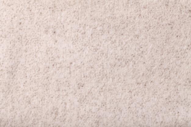 Lichtbeige pluizige achtergrond van zachte, wollige doek. textuur van roomtextiel.