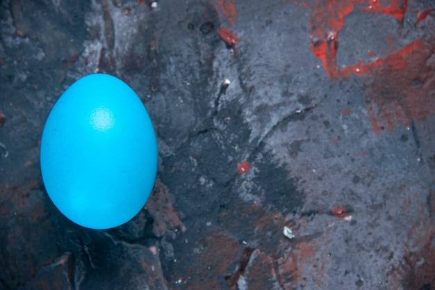 Lichtblauw ei aan de rechterkant op donkere mixkleuren verontruste achtergrond met vrije ruimte