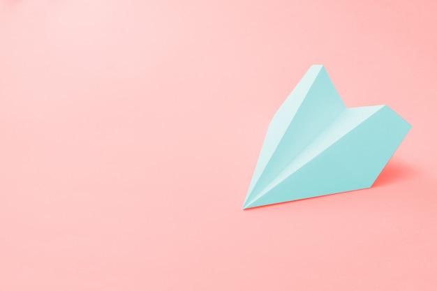Lichtblauw papieren vliegtuig op koraal