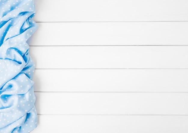 Lichtblauw stippen gevouwen tafelkleed over gebleekte houten tafel. bovenaanzicht afbeelding. copyspace