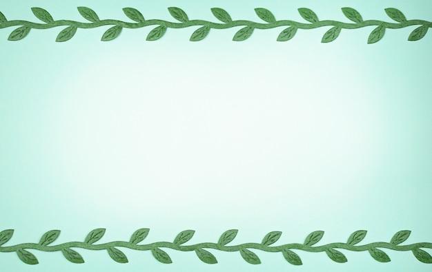Lichtblauwe achtergrond met een plek voor tekst en takken van groene bladeren aan de randen.