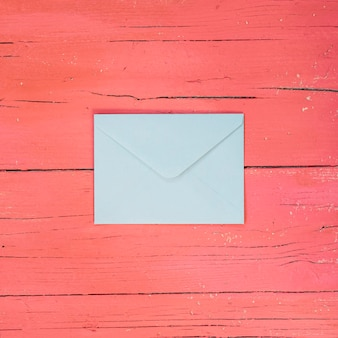 Lichtblauwe envelop op lichtroze houten ondergrond
