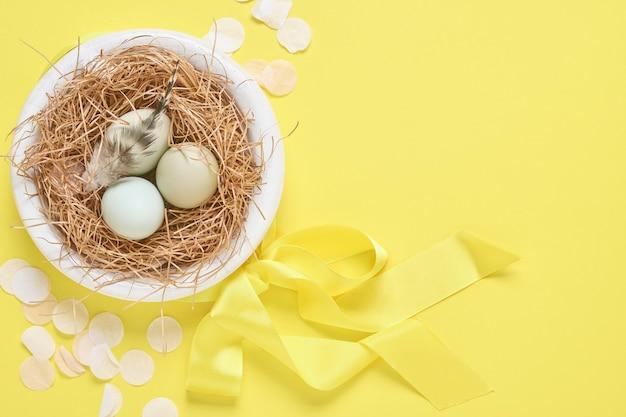 Lichtblauwe paaseieren in nest op gele trendkleur achtergrond. pasen minimale creatieve horizontale compositie met kopie ruimte. bovenaanzicht.