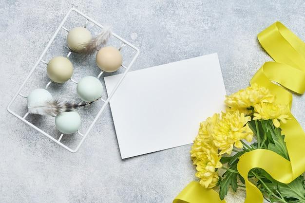 Lichtblauwe paaseieren in witte vintage metalen houder met veren en gele chrysantenbloemen op grijze achtergrond. bespotten.