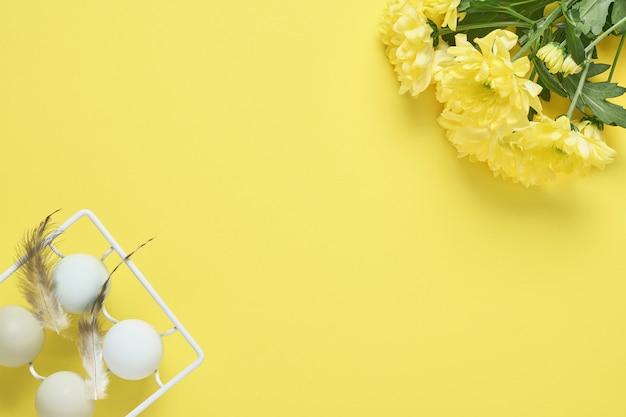 Lichtblauwe paaseieren in witte vintage metalen houder met veren en gele chrysantenbloemen. voorjaar