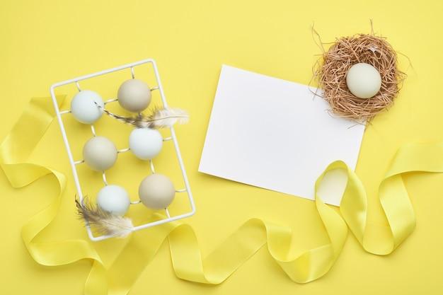Lichtblauwe paaseieren in witte vintage metalen houder met veren geel, klein nest, lint en blanco papier voor tekst op achtergrond. bovenaanzicht.