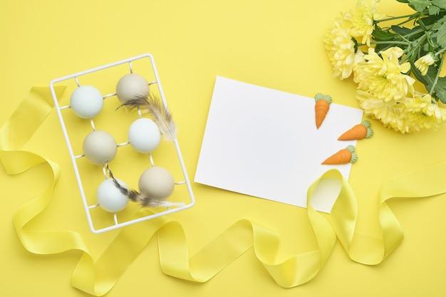 Lichtblauwe paaseieren in witte vintage metalen houder met veren, lint, gele chrysantenbloemen en blanco papier voor tekst op gele achtergrond. bespotten.