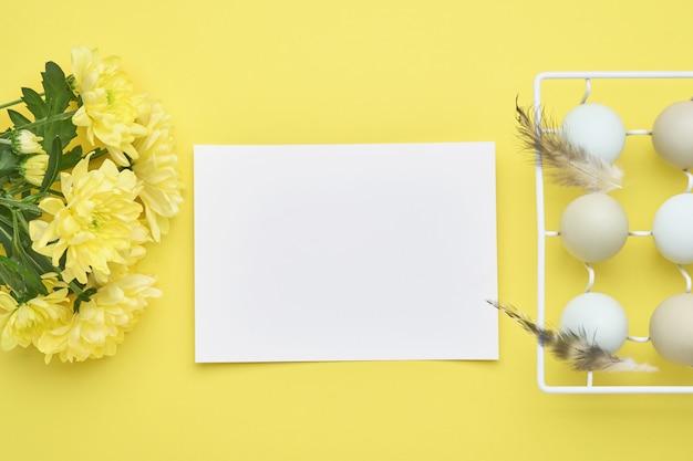 Lichtblauwe paaseieren in witte vintage metalen houder met veren, lint, gele chrysantenbloemen en blanco papier voor tekst op gele tafel.