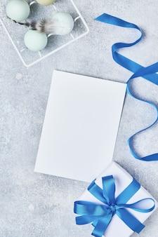 Lichtblauwe paaseieren met veren in witte vintage metalen houder en geschenkdoos met blauw lint en plaats voor tekst op grijze tafel. bovenaanzicht