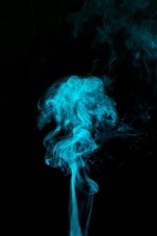 Lichtblauwe rook die tegen zwarte achtergrond blaast