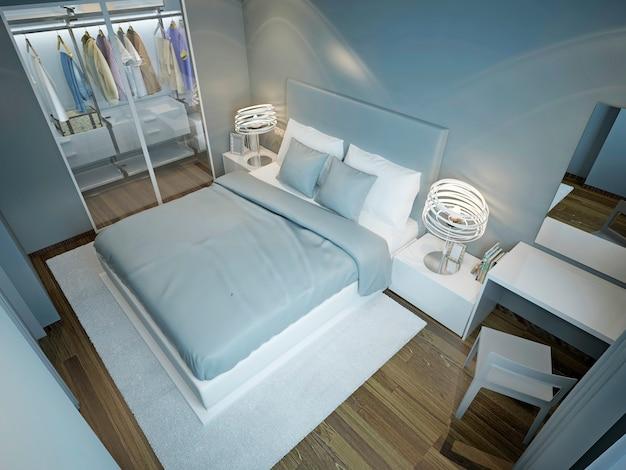Lichtblauwe slaapkamer met kleerkast en aangekleed bed met blauwe en witte kussens