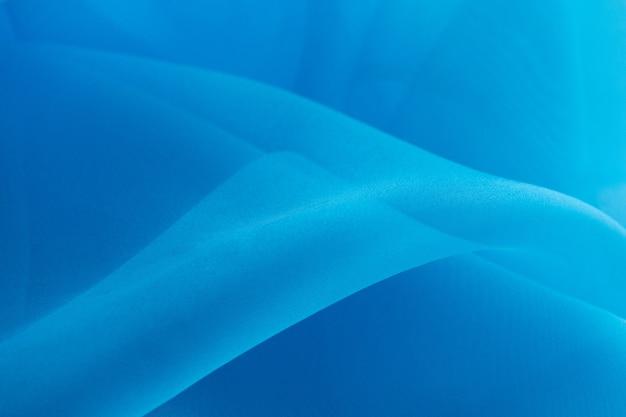 Lichtblauwe textuur die als achtergrond wordt gebruikt. blauwe lichte stof textuur. blauwe organza stof