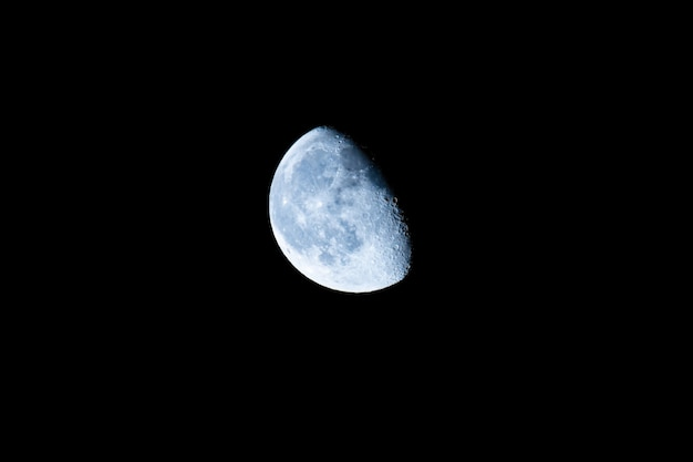 Lichtblauwe wassende maan in close-up.
