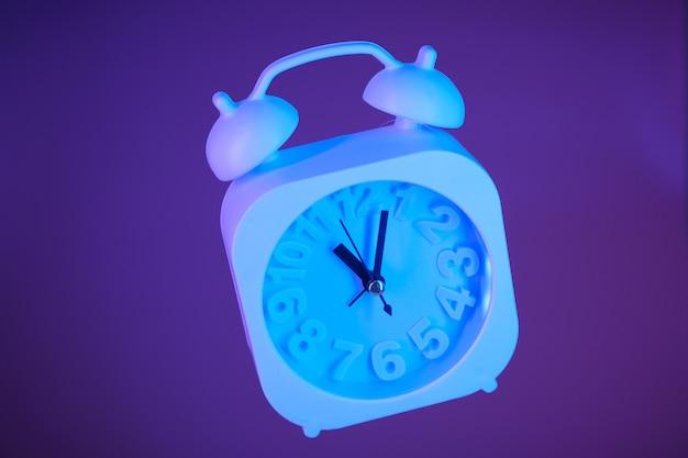 Lichtblauwe wekker die in lucht op een heldere purpere achtergrond wordt opgeschort
