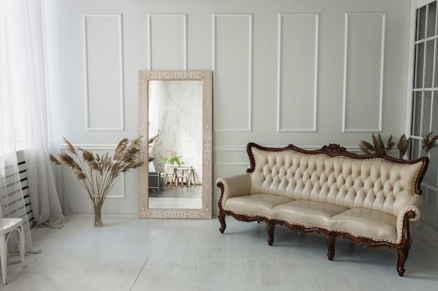 Lichtbruine houten spiegel met etnisch patroon in een lichte kamer met witte muren
