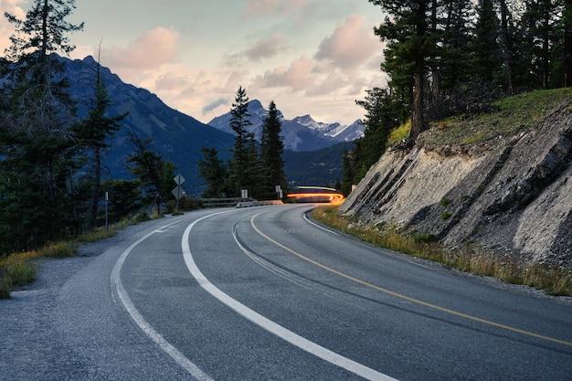 Lichte auto op snelweg met rotsachtige bergen in nationaal park banff