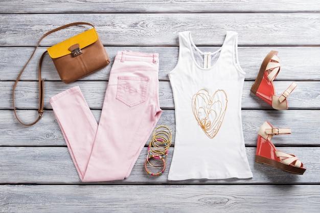 Lichte broek met witte top. tweekleurige portemonnee en sandalen met sleehak. vrouwelijke outfit en sieraden. set kleding op showcase.