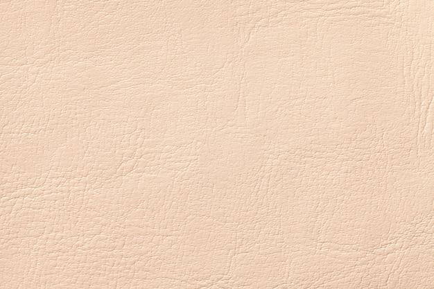 Lichte de textuurachtergrond van het koraalleer, close-up. beige gebarsten achtergrond
