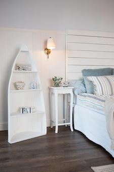 Lichte en comfortabele slaapkamer interieur in scandinavische stijl. bloemen op nachtkastje. kussen op bed decoratie kamer interieur. brandende kleine lamp boven een tafel.