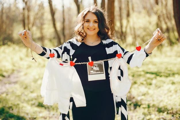 Lichte en gelukkige zwangere vrouw die in het zonnige park loopt