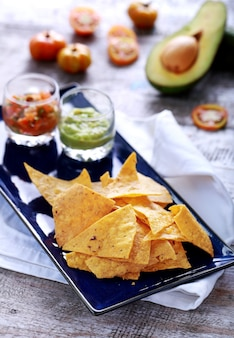 Lichte en knapperige maïschips geserveerd met salsa en guacamole op blauw bord