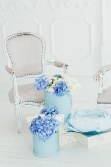 Lichte fauteuil in vintage stijl en dozen met bloemen