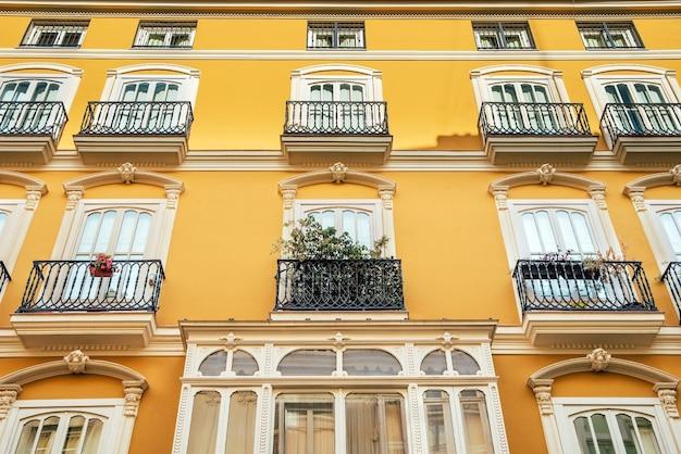 Lichte gevel van een typisch oud mediterraan gebouw geschilderd in heldere kleuren en warme tinten.