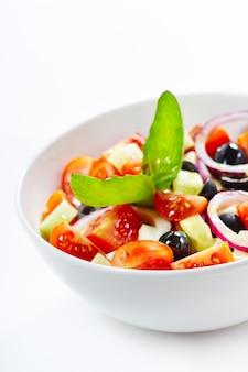 Lichte griekse salade met verse groenten, gegarneerd met basilicum.