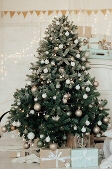 Lichte kamer interieur met versierde kerstboom en veel geschenkdozen.