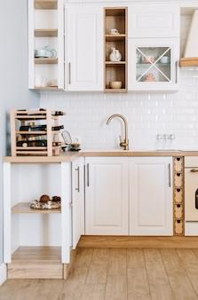 Lichte keuken in scandinavische stijl met borden en keukenaccessoires op tafel.