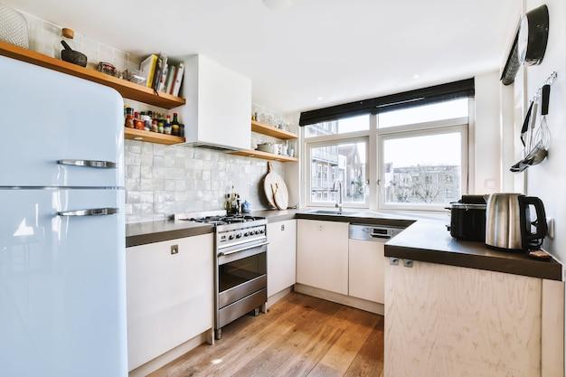 Lichte kleine woonkeuken met breed raam ingericht met kasten en planken met inbouwapparatuur in modern stadsappartement