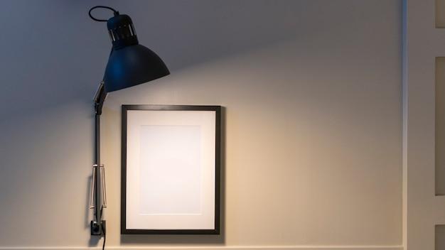 Lichte lamp met wit frame op de muur