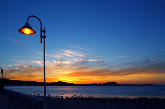 Lichte lantaarnpaal van het zonsondergang de oranje blauwe zeegezicht