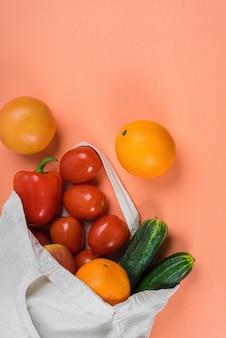 Lichte linnen eco-tas met verse groenten en fruit.