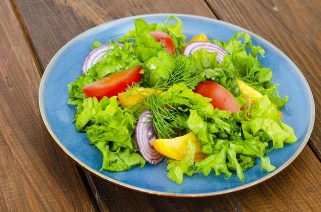 Lichte maaltijd van groene bladeren van sla, gele en rode tomaten, olijfolie op houten tafel.