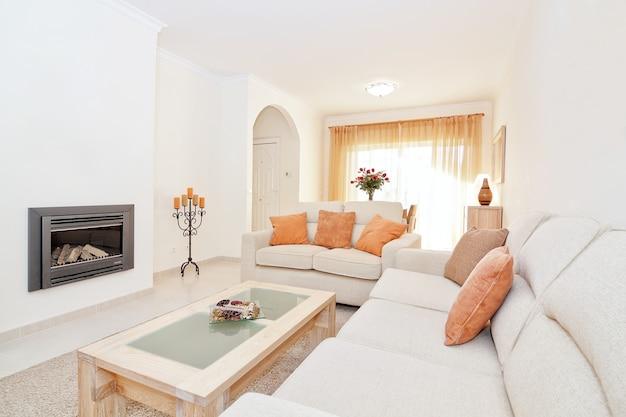 Lichte moderne woonkamer met openhaard voor verwarming. in de warme kleuren.